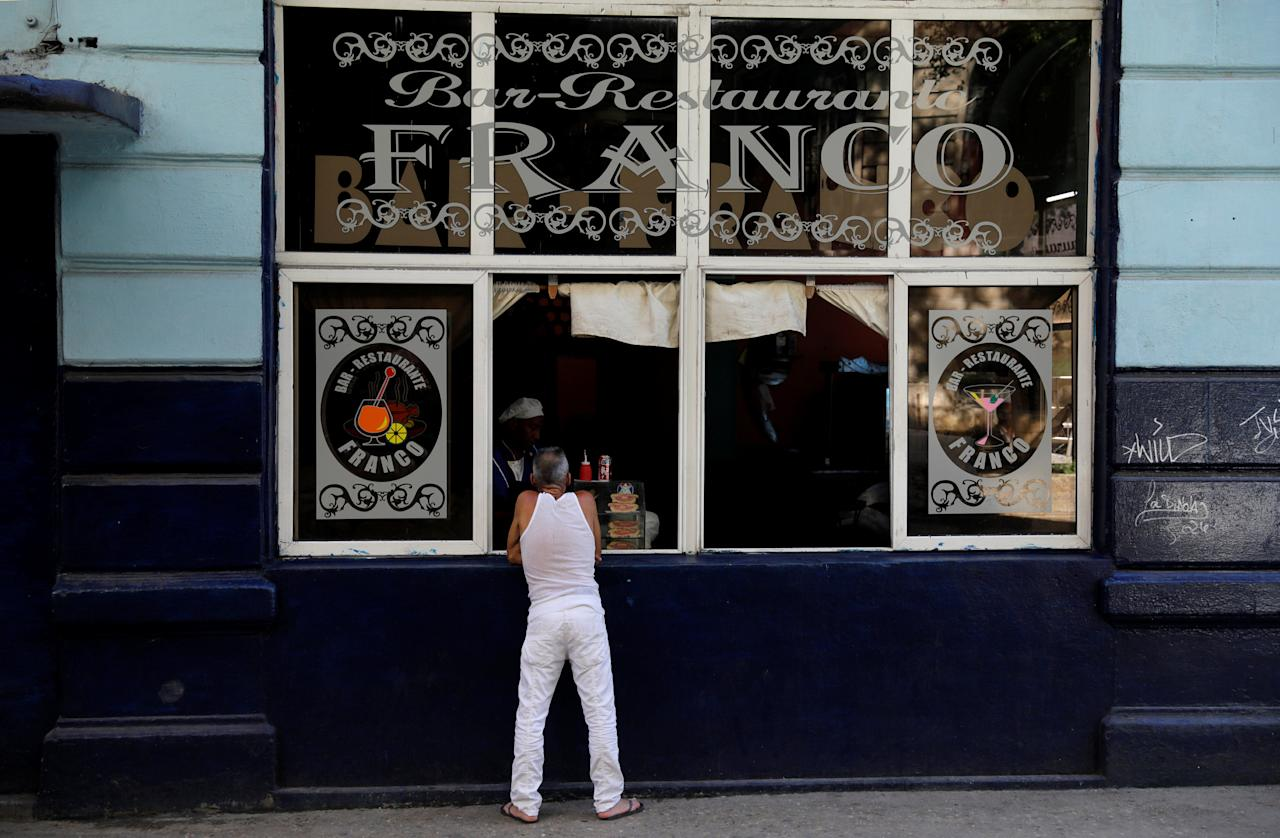 A man buys food from the window of a restaurant on the streets of Havana, Cuba, August 7, 2018. Picture taken August 7, 2018  REUTERS/Jim Bourg