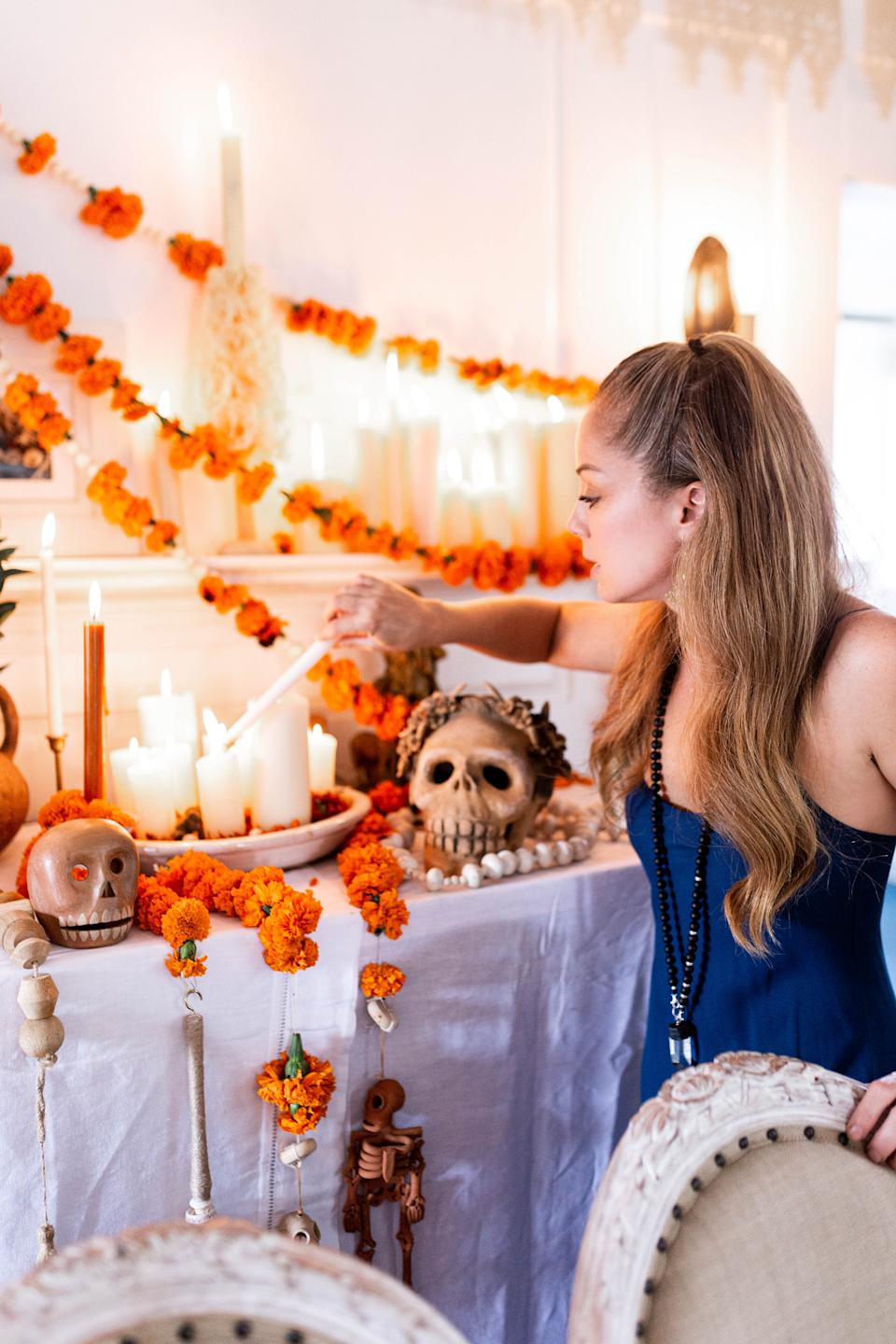 Marcela Valladolid lights a candle on her ofrenda, or altar. (Photo: Cecilia Martin Del Campo)