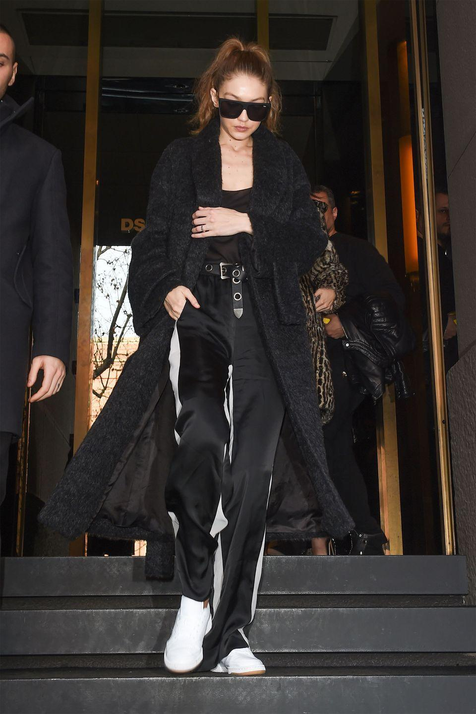 <p>In a black coat, top, belted silk sweatpants, white sneakers and sunglasses while out in Milan.</p>