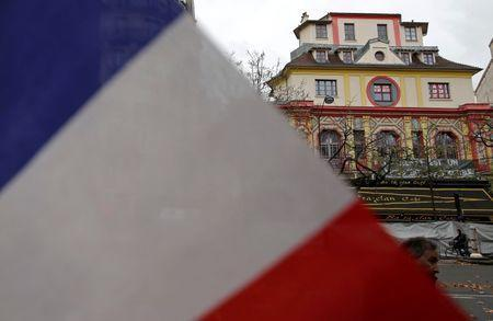 A French flag is seen in front of the Bataclan concert hall to pay tribute to the victims of the series of deadly attacks on Friday, in Paris, France, November 17, 2015. REUTERS/Christian Hartmann