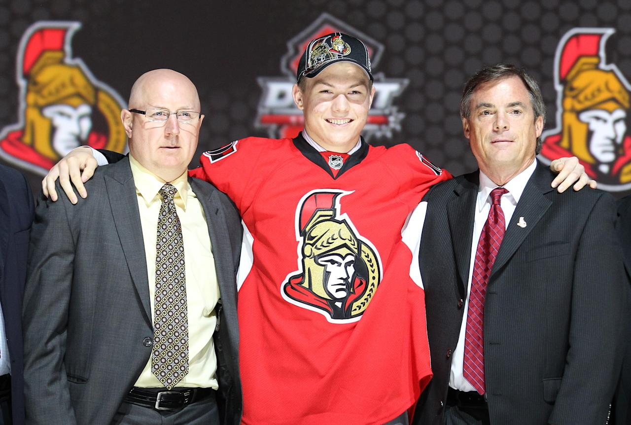 Jun 30, 2013; Newark, NJ, USA; Ryan Pulock poses for a photo with team officials after being introduced as the number fifteen overall pick to the New York Islanders during the 2013 NHL Draft at the Prudential Center. (Ed Mulholland-USA TODAY Sports)