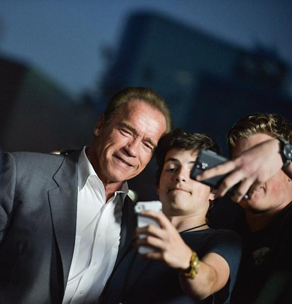 """FILE - This March 19, 2014 file photo shows actor and former California Gov. Arnold Schwarzenegger posing with fans at the LA Premiere of """"Sabotage,"""" in Los Angeles. (Photo by Richard Shotwell/Invision/AP, File)"""