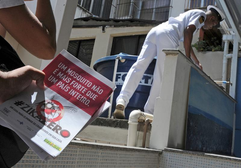 Armed forces personnel hand out flyers during an awareness campaign on the day of national mobilization against the Aedes aegypti mosquito in Rio de Janeiro on February 13, 2016