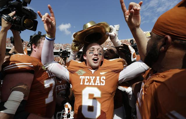 Texas quarterback Case McCoy (6) celebrates with teammates after their 36-20 win over Oklahoma in an NCAA college football game at the Cotton Bowl Saturday, Oct. 12, 2013, in Dallas. (AP Photo/LM Otero)