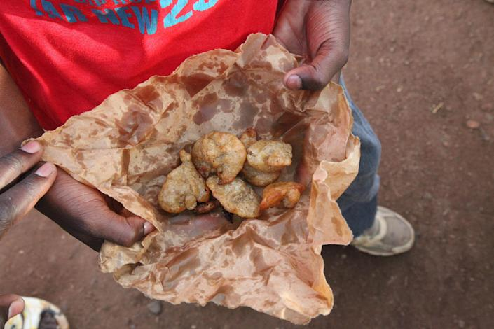 Mamadou Diagana, shows his fried donuts as he makes his way to school in Bamako, Mali, Tuesday, May 6, 2014. In Mali's capital, the majority of students go to neighborhood schools and return home from noon to 3 p.m. so they can eat lunch with their families. The they then return to class until 5 p.m. (AP Photo/Baba Ahmed)
