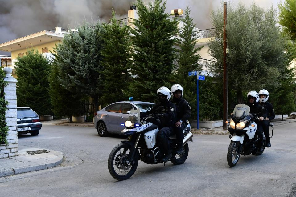 Policemen on motorcycles patrol during an evacuation of Adames area, northern Athens, Greece, Tuesday, Aug. 3, 2021. Hundreds of residents living near a forest area north of Athens fled their homes Tuesday as a wildfire reached residential areas as Greece grappled with its worst heatwave in decades. (AP Photo/Michael Varaklas)