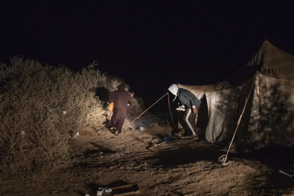 Smugglers walk past a tent that is used while building fishing boats intended to carry migrants to the Canary Islands, in a remote desert out of the town of Dakhla, in Morocco-administered Western Sahara, Tuesday, Dec. 22, 2020. (AP Photo/Mosa'ab Elshamy)