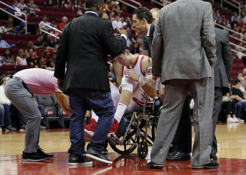 Houston Rockets forward Zhou Qi (9) is taken from the court in a wheelchair after injuring his left knee on a loose ball scramble play with Shanghai Sharks forward Luis Scola (4) during the first half of an exhibition NBA basketball game Tuesday, Oct. 9, 2018, in Houston. (AP Photo/Michael Wyke)