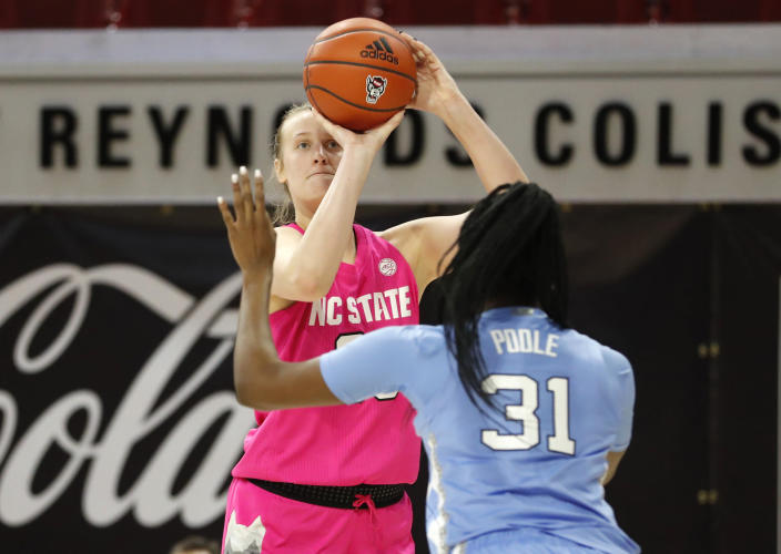 N.C. State's Elissa Cunane (33) shoots as North Carolina's Anya Poole (31) defends during the first half half of a college basketball game in the annual Play4Kay game at Reynolds Coliseum in Raleigh, N.C., Sunday, Feb. 21, 2021. (Ethan Hyman/The News & Observer via AP)