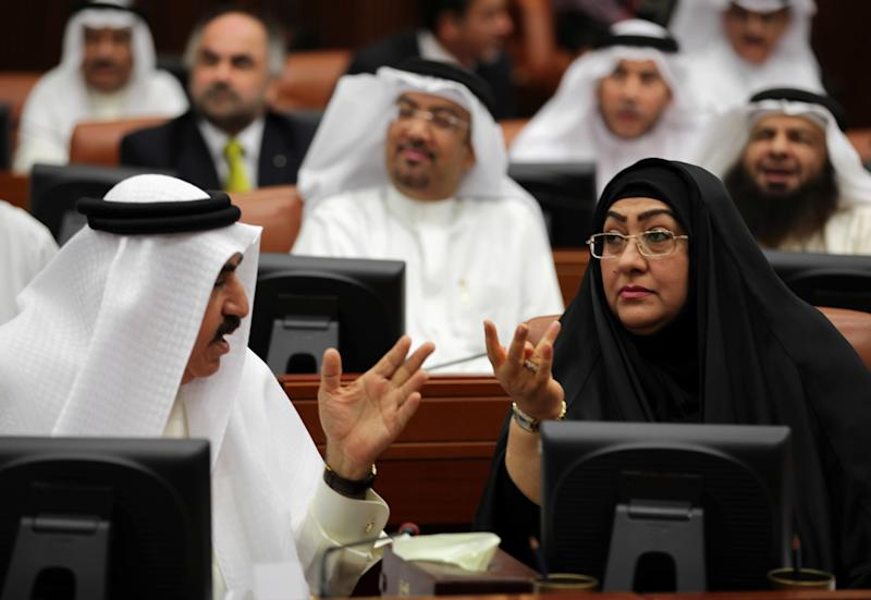 Bahraini lawmaker Latifa Gaould, right, talks with a colleague during a special session of parliament to discuss how to handle the uprising in the Gulf island kingdom, convened in Manama, Bahrain, Sunday, July 28, 2013. Several members of Bahrain's parliament, which doesn't include opposition groups, called for harsher methods against protesters, including stripping citizenship, establishing curfews, instituting martial law, employing the death penalty and banning all protests. (AP Photo/Hasan Jamali)