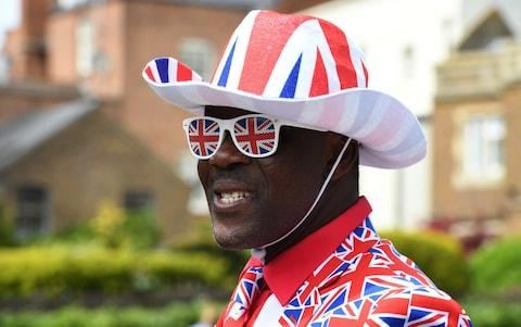 A man wears a Union Jack suit with matching hat and glasses as he waits 24 hours before for the procession on the Long Walk - Credit: James D. Morgan/Getty Images Europe