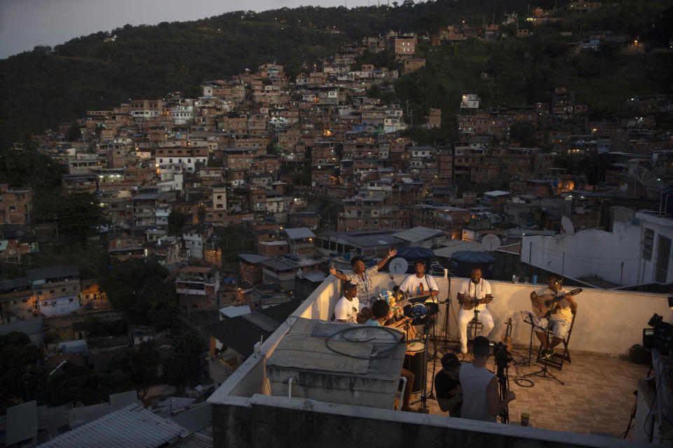 """Members of the """"Tempero de Criola"""" band perform amid the new coronavirus pandemic at the Turano favela, in Rio de Janeiro, Brazil, Friday, June 19, 2020. A group of musicians playing Samba offered a small concert to the residents of Turano favela, most of whom remain quarantined to curb the spread of COVID-19. Residents could watch the performance from their windows, balconies or via internet. (AP Photo/Silvia Izquierdo)"""