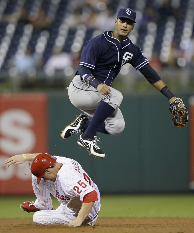 San Diego Padres shortstop Ronny Cedeno, top, leaps over Philadelphia Phillies' Cody Asche after forcing him out at second base on a double play hit into by Freddy Galvis during the eighth inning of a baseball game, Tuesday, Sept. 10, 2013, in Philadelphia. San Diego won 8-2. (AP Photo/Matt Slocum)