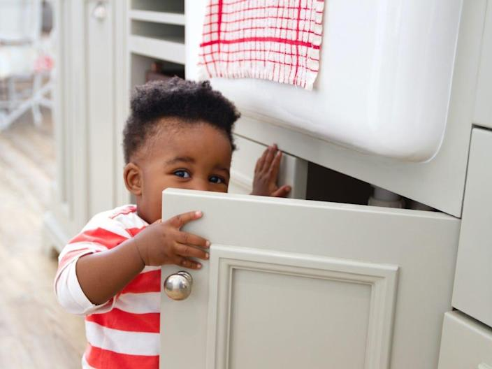 A child reaches into a kitchen cabinet filled with cleaning supplies.