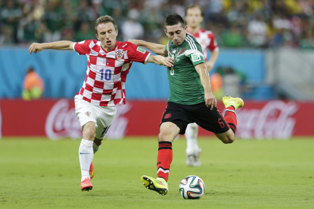 Mexico's Hector Herrera, right, gets in a shot despite the challenge of Croatia's Luka Modric during the group A World Cup soccer match between Croatia and Mexico at the Arena Pernambuco in Recife, Brazil, Monday, June 23, 2014. (AP Photo/Petr David Josek)
