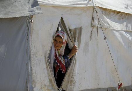 A Syrian refugee woman looks out from her tent at Suleymansah refugee camp in Akcakale in Sanliurfa province, Turkey, June 11, 2015. REUTERS/Osman Orsal