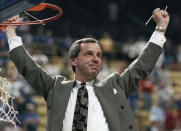 FILE - In this March 27, 1993, file photo, then-Kansas coach Roy Williams raises his arms in victory after cutting a piece of the net after the NCAA Midwest Regional final in St. Louis. Williams' Jayhawks defeated Indiana 83-77 to advance to the Final Four in New Orleans. North Carolina announced Thursday, April 1, 2021, that Hall of Fame basketball coach Roy Williams is retiring after a 33-year career that includes three national championships. (AP Photo/Seth Perlman, File)
