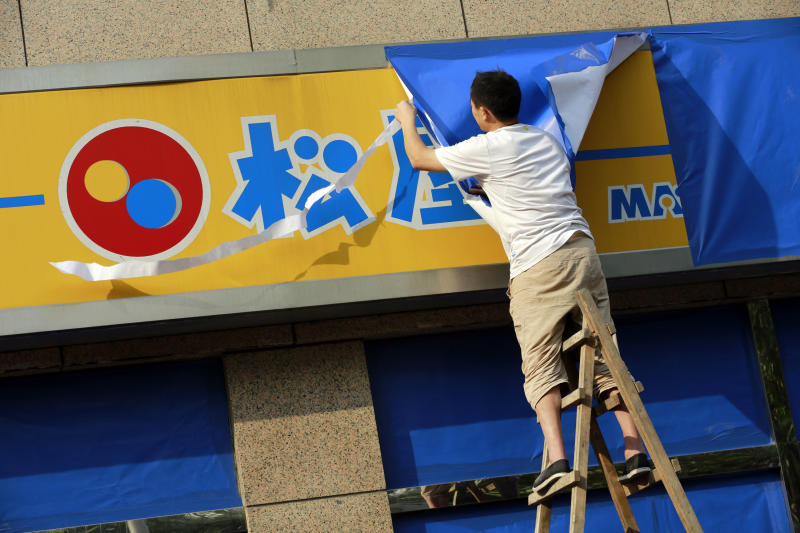 FILE - In this Monday, Sept. 17, 2012 file photo, A worker covers a signboard of a Japanese restaurant chain with blue sheets ahead of major protests expected on Tuesday, Sept. 18 near the Japanese Consulate General in Shanghai, China. Scores of Japanese-owned factories and stores in China were shuttered Tuesday as anti-Japanese demonstrations raged in dozens of cities. At stake are billions of dollars in investments and far more in sales and trade between Japan and China, the world's third- and second-largest economies. The two are so closely entwined, though, that both would suffer from any long-term disruptions. (AP Photo/Eugene Hoshiko, File)