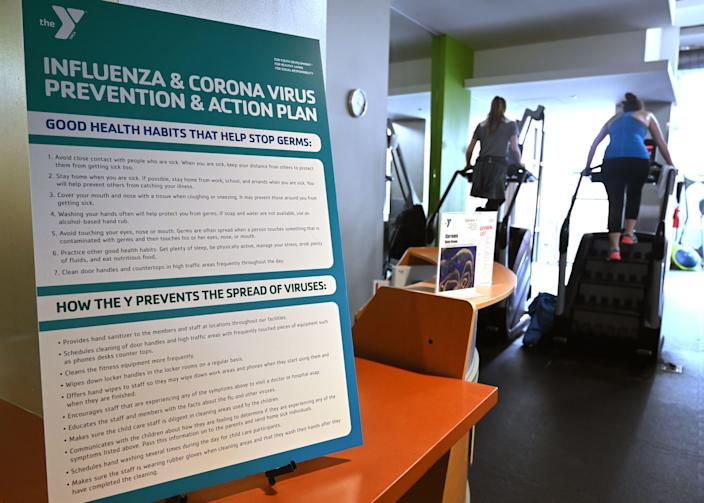 A poster informs guests about health habits and an action plan to fight the coronavirus as people exercise at a YMCA community center and gym in Washington, DC on March 12, 2020. (Photo by EVA HAMBACH/AFP via Getty Images)