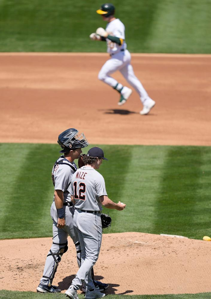 Tigers pitcher Casey Mize and catcher Grayson Greiner talk on the mound as Athletics left fielder Mark Canha, top, rounds the bases after hitting a solo home run during the second inning on Saturday, April 17, 2021, in Oakland, California.
