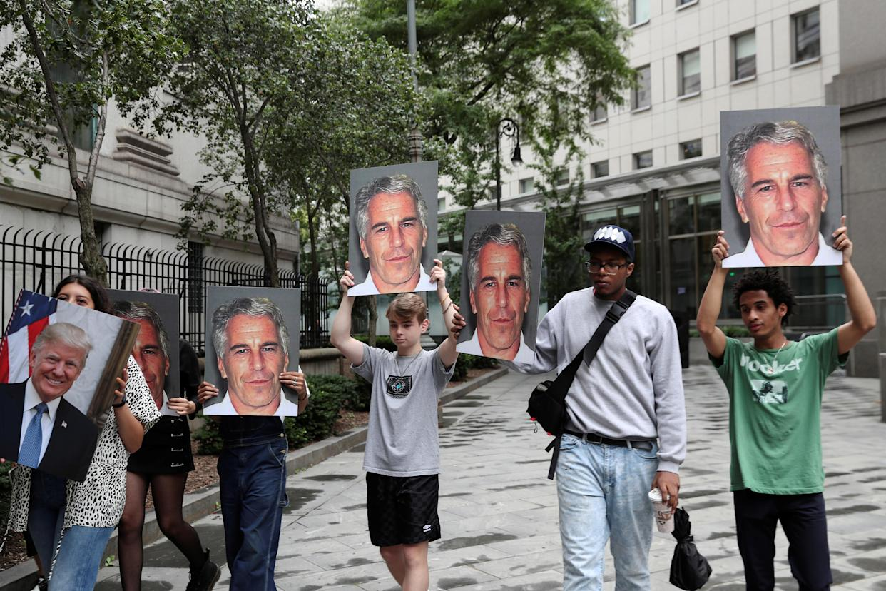 Demonstrators holding signs protesting Jeffrey Epstein on July 8, as he awaited arraignment in the Southern District of New York on sex trafficking charges. (Photo: Shannon Stapleton/Reuters)