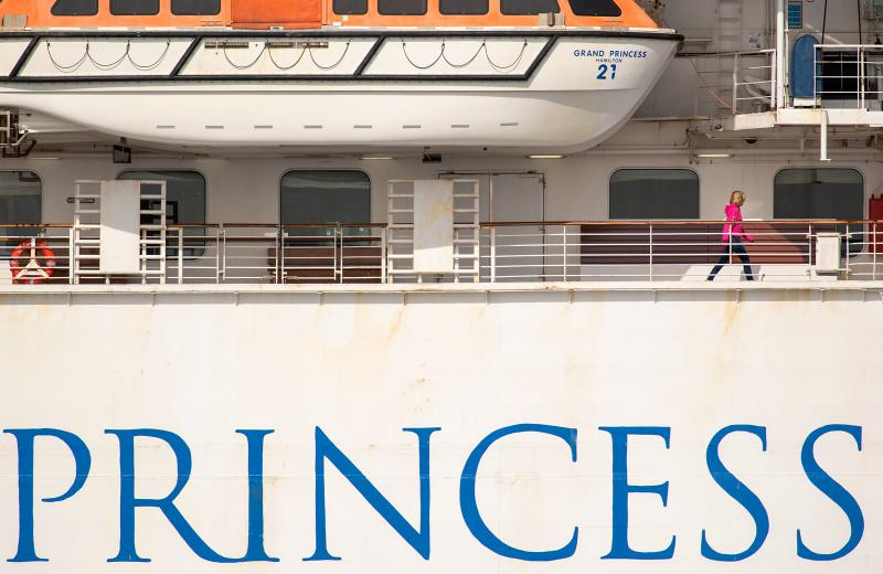 A passenger walks along the Grand Princess cruise ship, operated by Princess Cruises, as it maintains a holding pattern about 25 miles off the coast of San Francisco, California on March 8, 2020. - California prepared to disembark passengers from a virus-hit cruise ship as officials played down any risk to local communities.The Grand Princess, which has 21 novel coronavirus infections among the 3,500 people on board, is set to dock in Oakland Monday after four days held off the coast of nearby San Francisco. (Photo by Josh Edelson / AFP) (Photo by JOSH EDELSON/AFP via Getty Images)