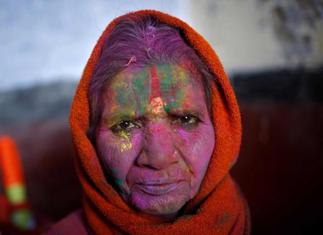 A widow with her face smeared with coloured powder watches the Holi celebrations organised by non-governmental organisation Sulabh International at a widows' ashram in Vrindavan in the northern Indian state of Uttar Pradesh March 14, 2014. Traditionally in Hindu culture, widows are expected to renounce earthly pleasure so they do not celebrate Holi. But women at the shelter for widows, who have been abandoned by their families, celebrated the festival by throwing flowers and coloured powder. Holi, also known as the Festival of Colours, heralds the beginning of spring and is celebrated all over India. REUTERS/Ahmad Masood (INDIA - Tags: ANNIVERSARY RELIGION SOCIETY)