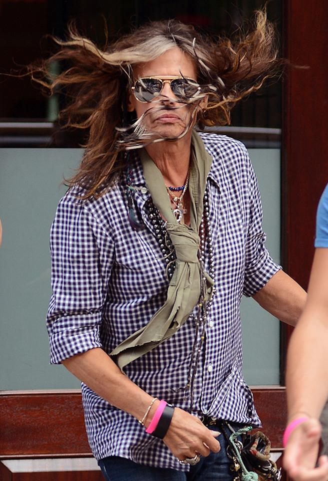 June 11, 2013: Steven Tyler pictured today leaving his hotel in New York City while his wind blown hair covers his face. 