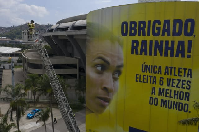 Firefighter Elielson Silva plays his trumpet, with the Maracana stadium in the background
