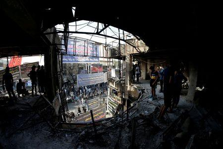 Sunni and Shi'ite Muslims attend prayers during Eid al-Fitr at the site of a suicide car bomb attack over the weekend at the shopping area of Karrada, in Baghdad