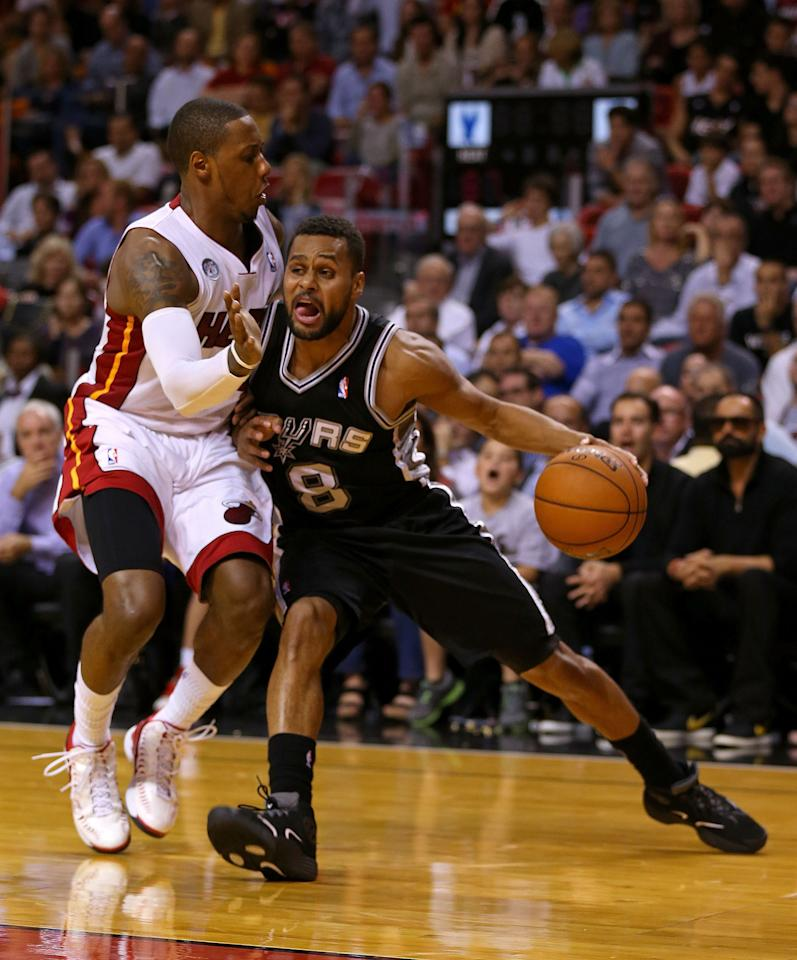 MIAMI, FL - NOVEMBER 29: Patrick Mills #8 of the San Antonio Spurs drives on Mario Chalmers #15 of the Miami Heat during a game  at American Airlines Arena on November 29, 2012 in Miami, Florida.  (Photo by Mike Ehrmann/Getty Images)