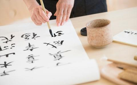 Female hands and japanese calligraphy - Credit: Tetra Images