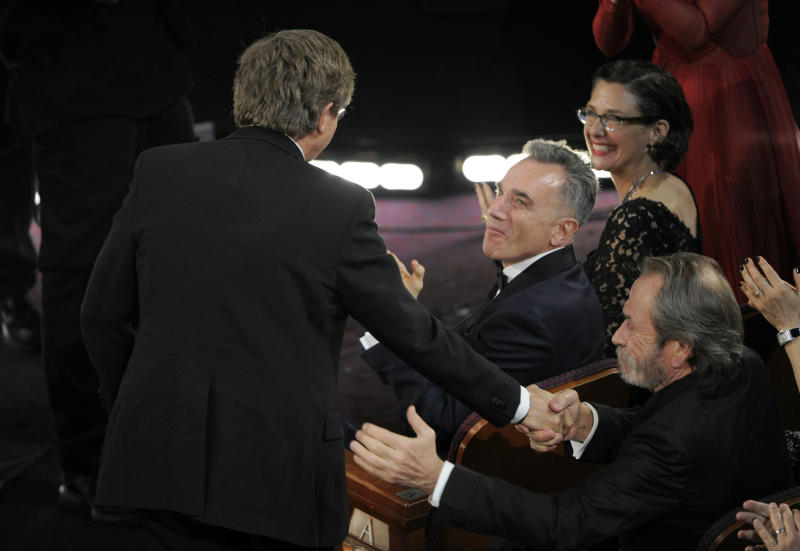 "From right, Tommy Lee Jones and Daniel Day Lewis congratulate Rick Carter as Carter walks on stage to accept the award for best production design for ""Lincoln"" during the Oscars at the Dolby Theatre on Sunday Feb. 24, 2013, in Los Angeles. (Photo by Chris Pizzello/Invision/AP)"