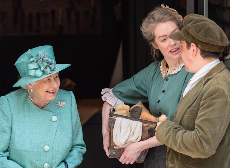 Queen Elizabeth II speaks to actors in period costume during a visit to Covent Garden, London, where she viewed a replica of one of the original Sainsbury's stores.