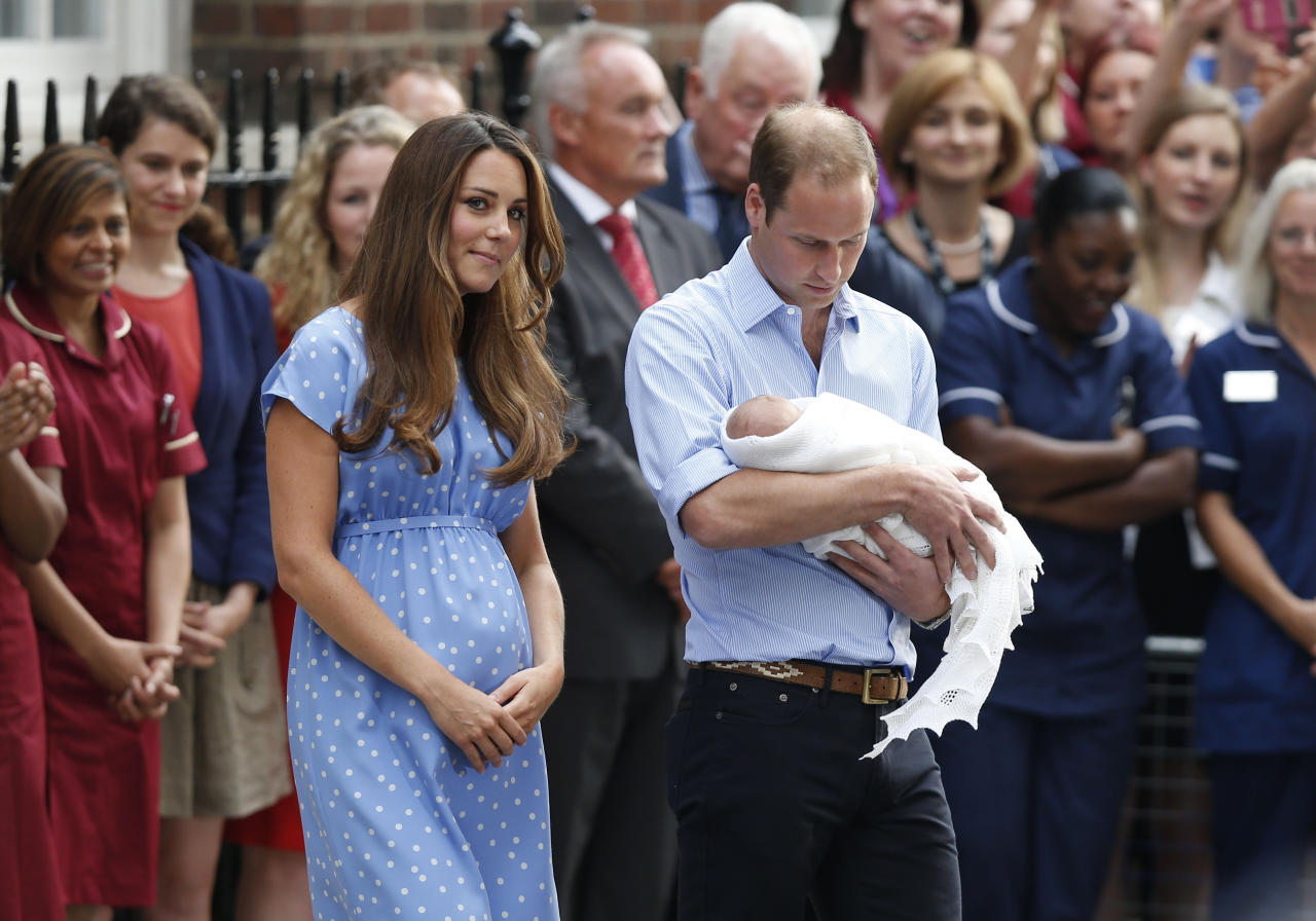 This July 23, 2013 file photo shows Britain's Prince William, right, and Kate, Duchess of Cambridge with the Prince of Cambridge as they pose for photographers outside St. Mary's Hospital in London. Princess Diana wore a caftan-like outfit that hid the post-childbirth tummy bump when William was born. In contrast, the former Kate Middleton, in her first public appearance on July 23, 2013, after giving birth, wore a dress that did not camouflage her belly, and many women are applauding her choice. (AP Photo/Sang Tan, File)