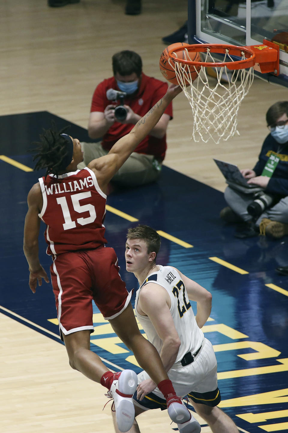 Oklahoma guard Alondes Williams (15) shoots over West Virginia guard Sean McNeil (22) during the first half of an NCAA college basketball game Saturday, Feb. 13, 2021, in Morgantown, W.Va. (AP Photo/Kathleen Batten)