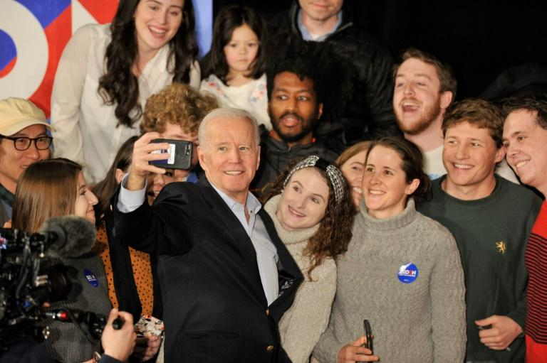 Former vice president Joe Biden takes selfies with supporters after speaking at a rally in Manchester, New Hampshire