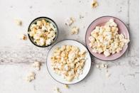 """<p>""""Popcorn is very low in calories yet high in fiber, making it one of the best weight loss-friendly snacks available,"""" says Dr. Axe. """"Instead of opting for microwave bags laden with chemicals and unhealthy additives, try making your own at home. Air-popped popcorn is easy to make and can be seasoned with ingredients like garlic powder, cayenne pepper or nutritional yeast to bump up the health benefits."""" For a little more guidance, try this <a href=""""https://www.prevention.com/food-nutrition/recipes/a20530460/garlic-chili-popcorn/"""" rel=""""nofollow noopener"""" target=""""_blank"""" data-ylk=""""slk:Garlic Chili Popcorn"""" class=""""link rapid-noclick-resp"""">Garlic Chili Popcorn</a> recipe.</p>"""
