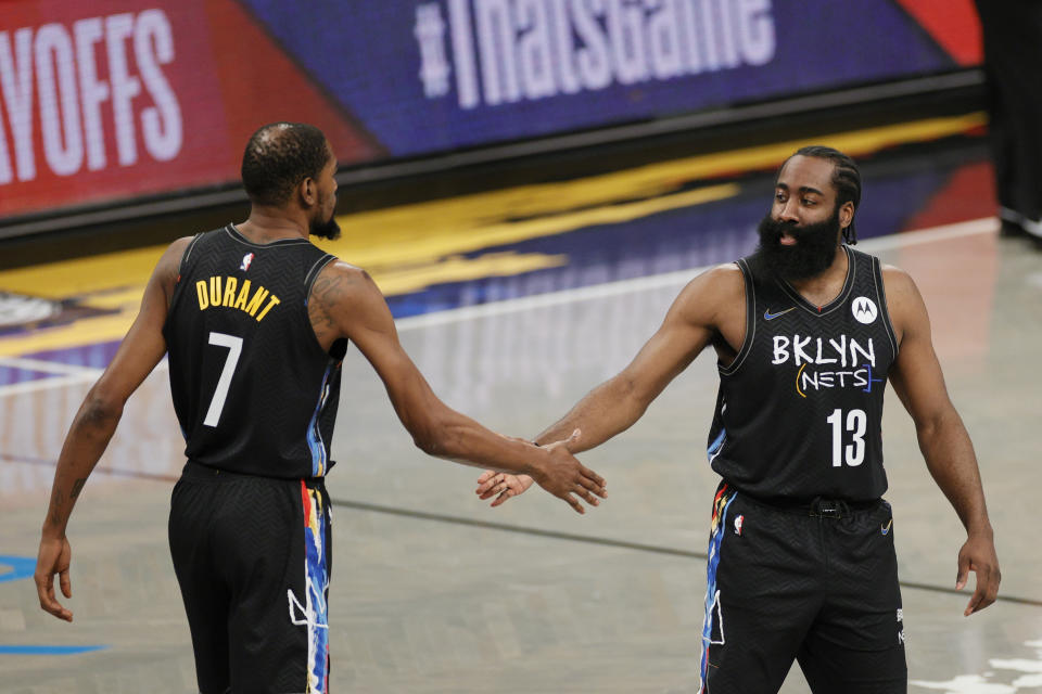 Kevin Durant high-fives James Harden of the Brooklyn Nets.