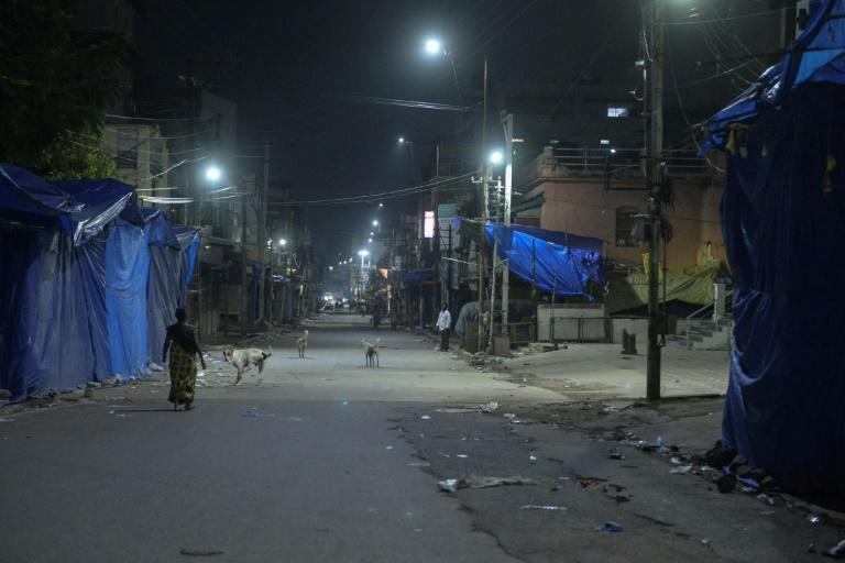 Lockdowns and nightly curfews have returned to several parts of India amid a surge in coronavirus cases -- here, a woman walks on an otherwise deserted street in Hyderabad