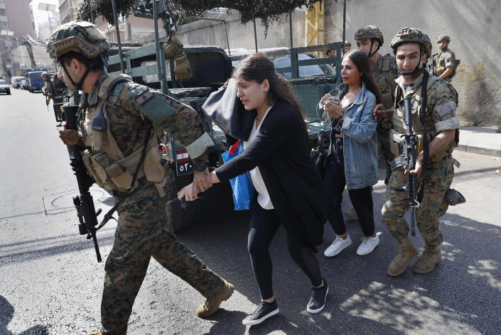Lebanese army special forces soldiers assist teachers as they flee their school after deadly clashes erupted nearby along a former 1975-90 civil war front-line between Muslim Shiite and Christian areas at Ain el-Remaneh neighborhood, in Beirut, Lebanon, Thursday, Oct. 14, 2021. Armed clashes broke out in Beirut Thursday during the protest against the lead judge investigating last year's massive blast in the city's port, as tensions over the domestic probe boiled over. (AP Photo/Hussein Malla)