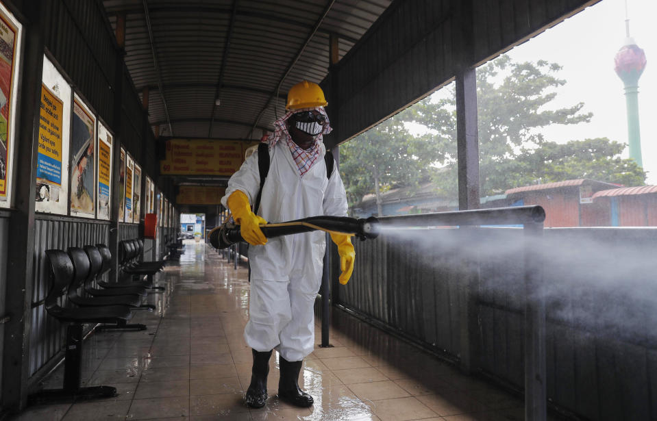 A Sri Lankan worker sprays disinfectants at a bus terminal to prevent the spread of coronavirus in Colombo, Sri Lanka, Monday, Oct. 26, 2020. To contain the spread, the government has closed schools and banned gatherings across Sri Lanka, and a curfew is in effect in many parts of Western province, where the infections have been concentrated. (AP Photo/Eranga Jayawardena)