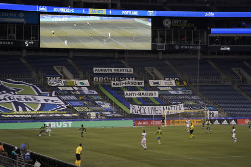 The Seattle Sounders and Portland Timbers play during the first half of an MLS soccer match in front of what is usually the supporters section, Sunday, Sept. 6, 2020, in Seattle at CenturyLink Field. Due to the coronavirus pandemic, matches are being played without fans in the stands, but members of the Emerald City Supporters and other groups were allowed to place flags and banners in the section. (AP Photo/Ted S. Warren)