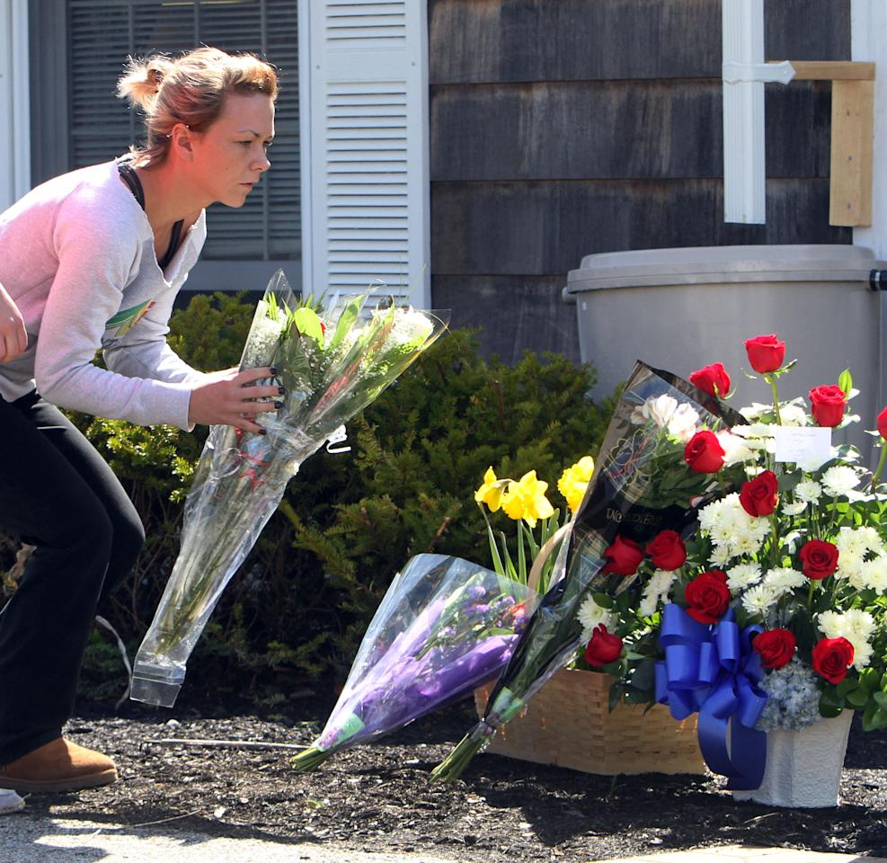 Samantha Flood places flowers at a makeshift memorial in front of the Town Hall for slain Police Chief Michael Maloney , Friday, April 13, 2012 in Greenland, N.H. Maloney was shot and killed Thursday when he and other officers entered a house during a drug raid. Four other police officers were wounded. Attorney General Michael Delaney says a police robot detected the bodies of suspect Cullen Mutrie and an unidentified woman in the house. He says both died of gunshot wounds. (AP Photo/Jim Cole)