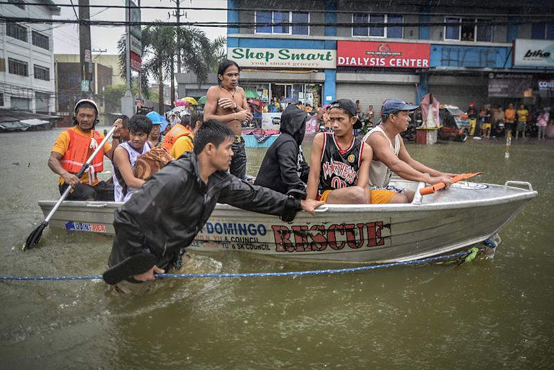 Flood victims are evacuated in a rescue boat after their homes were swamped by heavy flooding in Quezon city, suburban Manila, Philippines, Sept. 19, 2014. | NurPhoto—Corbis via Getty Images