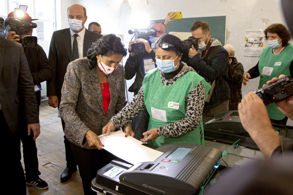 Georgia's President Salome Zurabishvili, center left, wearing a face mask to help curb the spread of the coronavirus, casts her ballot at a polling station during national municipal elections in Tbilisi, Georgia, Saturday, Oct. 2, 2021. Former President Mikheil Saakashvili was arrested after returning to Georgia, the government said Friday, a move that came as the ex-leader sought to mobilize supporters ahead of the national municipal elections seen as critical to the country's political makeup. The elections started Saturday. (AP Photo/Zurab Tsertsvadze)