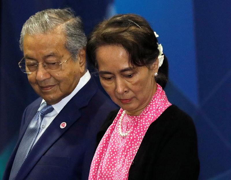 Tun Dr Mahathir Mohamad and Myanmar's leader Aung San Suu Kyi look for their positions during a group photo at the Asean-China Summit in Singapore November 14, 2018. — Reuters pic