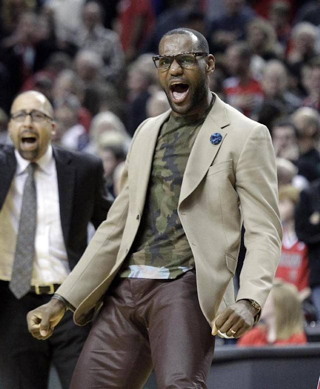 Miami Heat forward LeBron James, who did not play, celebrates after the Heat won an NBA basketball game against the Portland Trail Blazers in Portland, Ore., Saturday, Dec. 28, 2013. The Heat won 108-107. (AP Photo/Don Ryan)