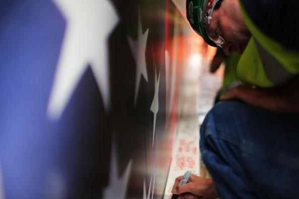 Construction worker Ken Apple signs the last steel beam, along with other members of the crews that helped build the tower, before it is hoisted 977 feet to the top of Four World Trade Center on June 25, 2012 in New York City. The trapezoidal glass and steel office building, which is designed as an architectural backdrop to the September 11 Memorial, is scheduled to open in 2013. (Photo by Spencer Platt/Getty Images)