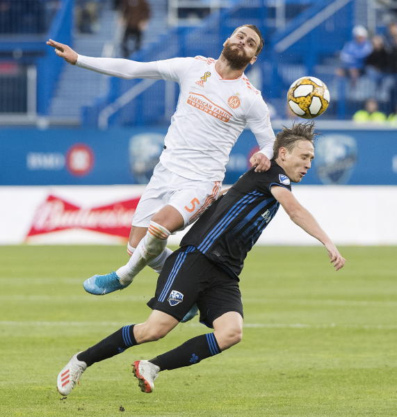 Atlanta United's Leandro Gonzalez Pirez, left, challenges Montreal Impact's Lassi Lappalainen during first half MLS soccer action in Montreal, Sunday, Sept. 29, 2019. (Graham Hughes/The Canadian Press via AP)